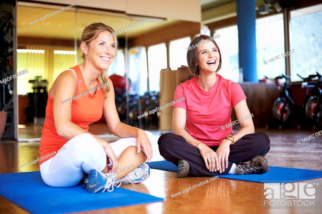 Stock Photo: Coach and client sitting cross-legged on floor in fitness studio.
