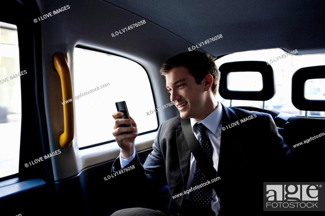 Stock Photo: A businessman in a taxi, using his mobile phone.