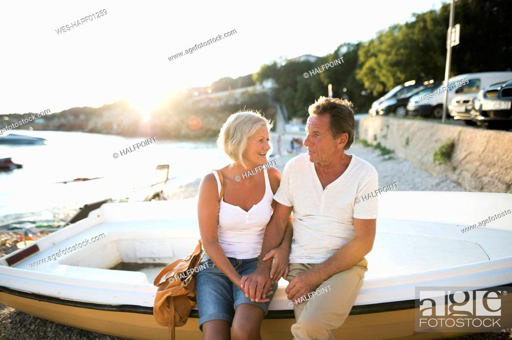 Photo de stock: Senior couple sitting on edge of a boat on the beach at evening twilight.