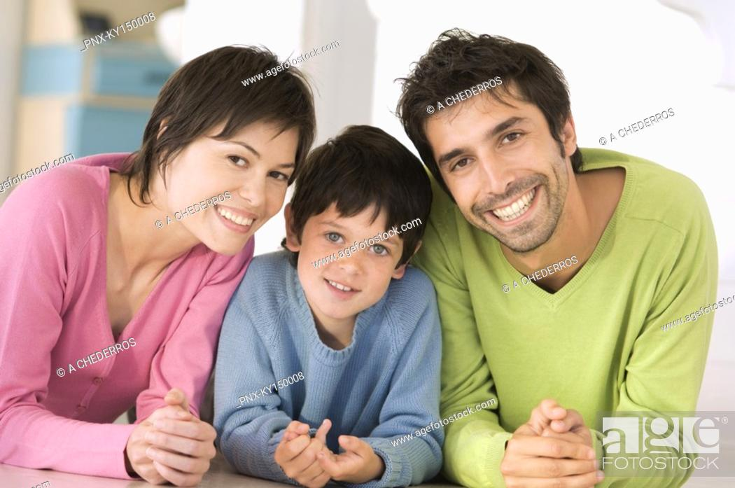 Stock Photo: Parents and son smiling for the camera, lying on floor.