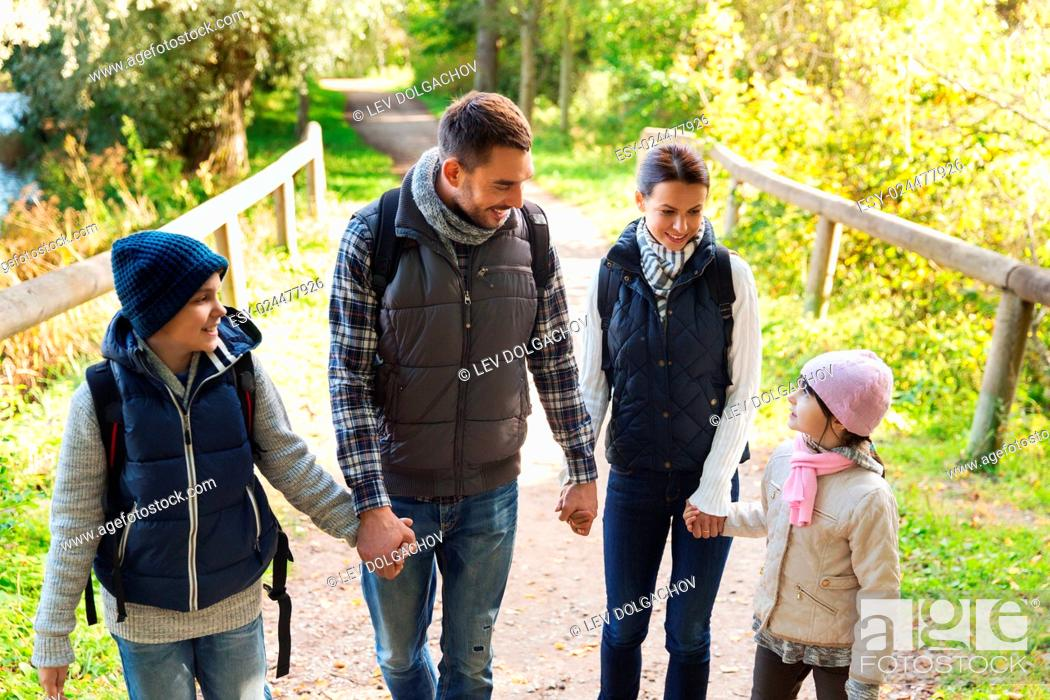 Stock Photo: adventure, travel, tourism, hike and people concept - happy family walking with backpacks in woods.