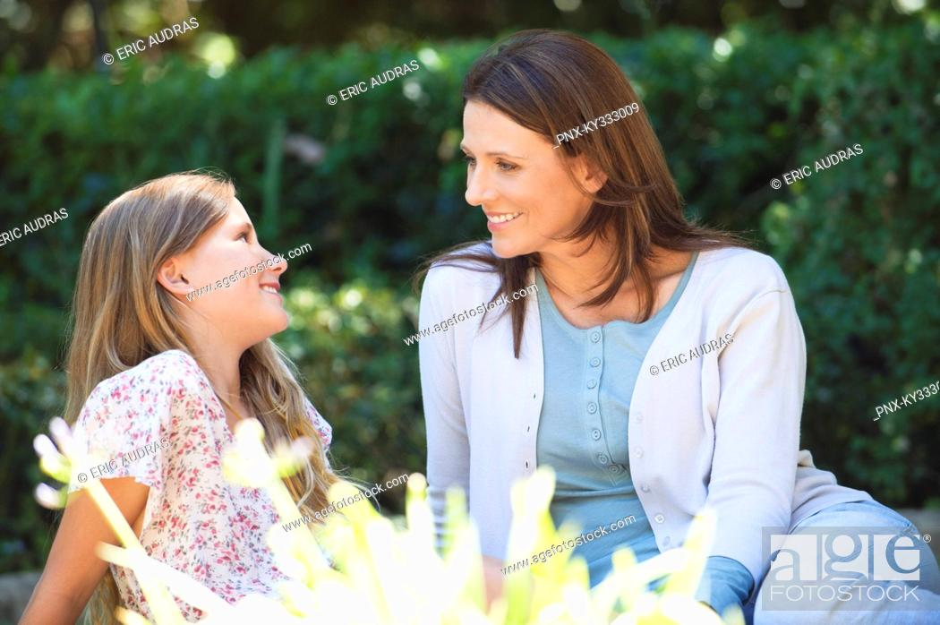 Stock Photo: Cute little girl and her mother sitting together in the garden.