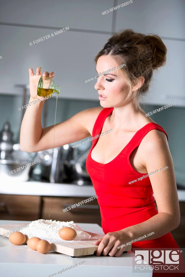 Stock Photo: Germany, Young woman pouring oil in flour.