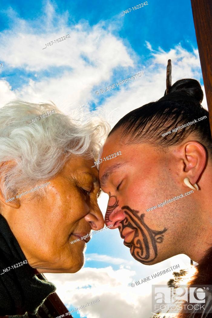 Stock Photo: A Maori man with ta moko facial tattoo and an elderly Maori woman doing hongi traditional Maori greeting , Te Puia New Zealand Maori Arts & Crafts Institute.