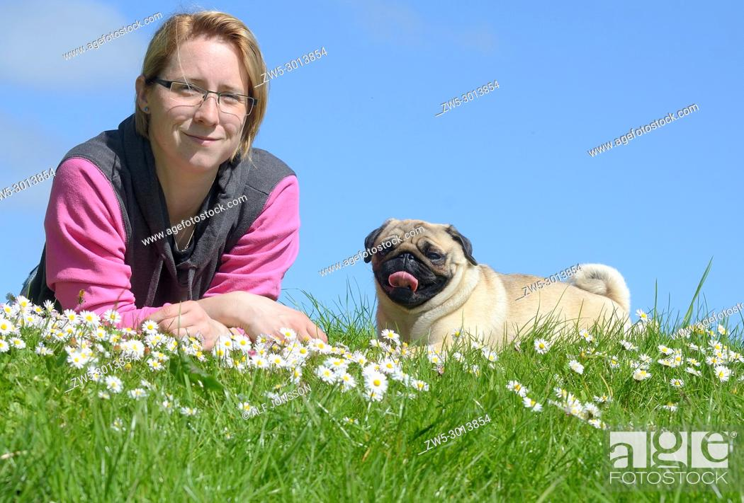 Photo de stock: Young woman lying with a pug dog on a green and with a blue sky in Ystad, Scania, Sweden.