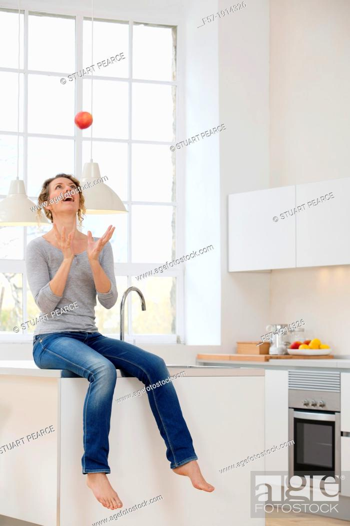 Stock Photo: Healthy young woman throwing an apple into the air.