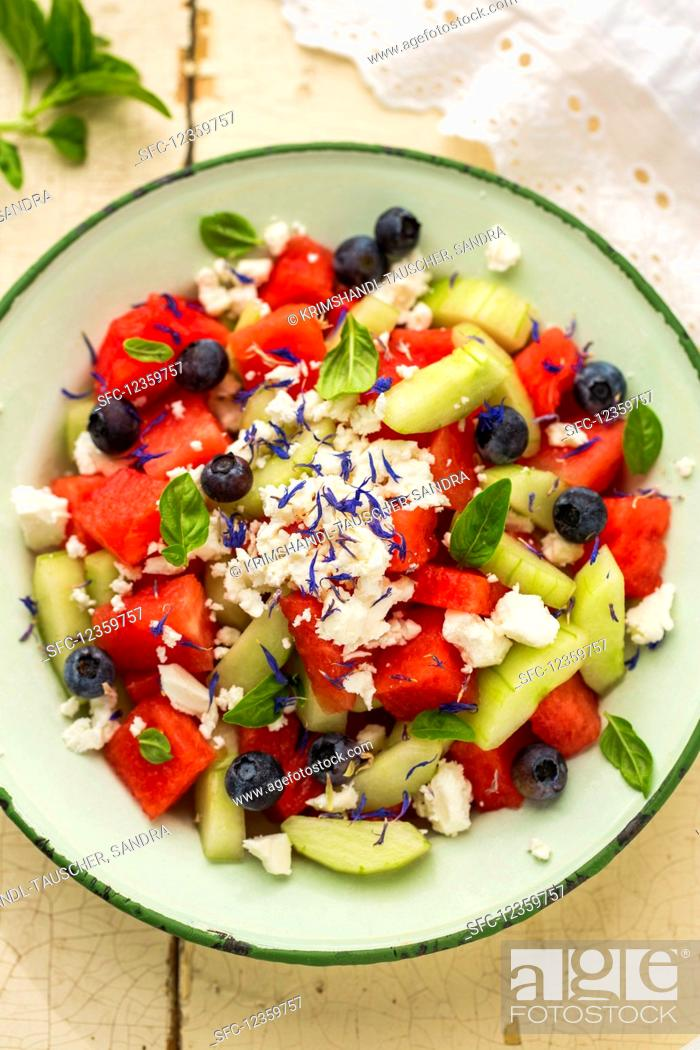 Stock Photo: Watermelon salad with blueberries, feta, cucumber, basil and cornflower blossoms.