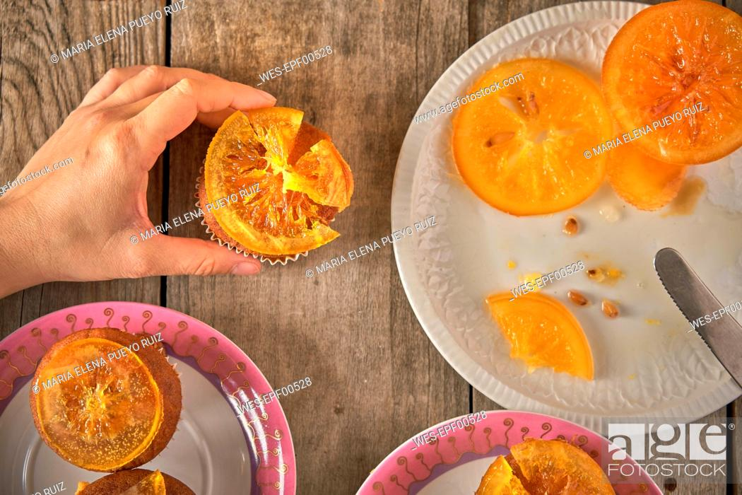 Stock Photo: Woman's hand garnishing muffins with candied orange slices.