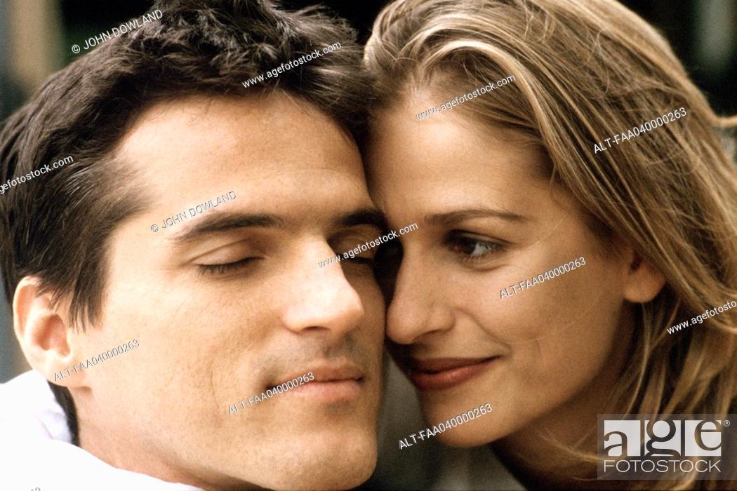 Stock Photo: Couple cheek to cheek, smiling, man\'s eyes closed.