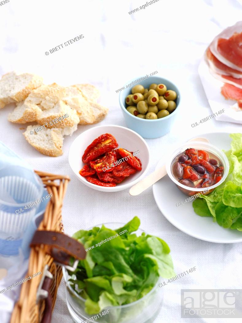 Stock Photo: Bowls of preserves, bread ad lettuce.