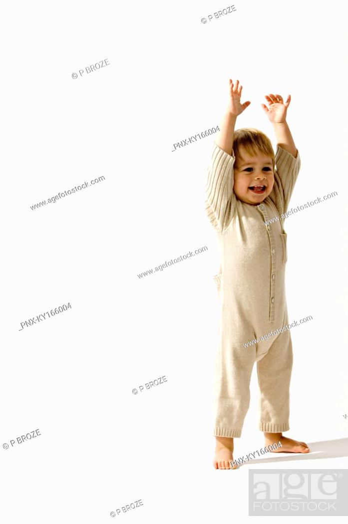 Stock Photo: Baby boy standing with his arms raised and smiling.