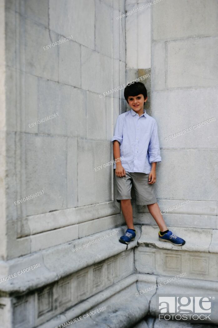 Stock Photo: portrait of 10 year old child with stone wall background of a cathedral.