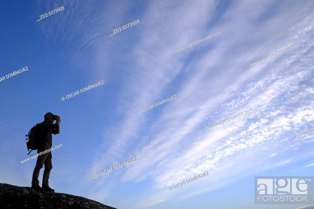 Stock Photo: Birdwatcher silhouetted against clouds. Taejo International Park. Extremadura. Spain.