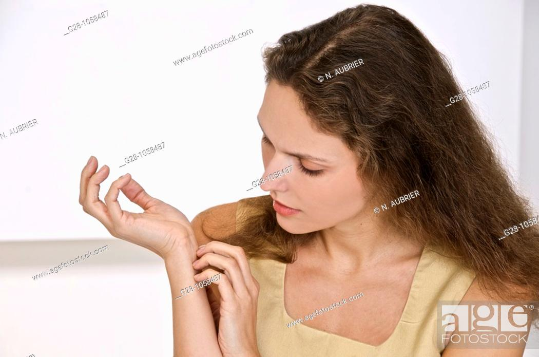 Stock Photo: young woman scratching the inside of her wrist  because of an itching sensation.