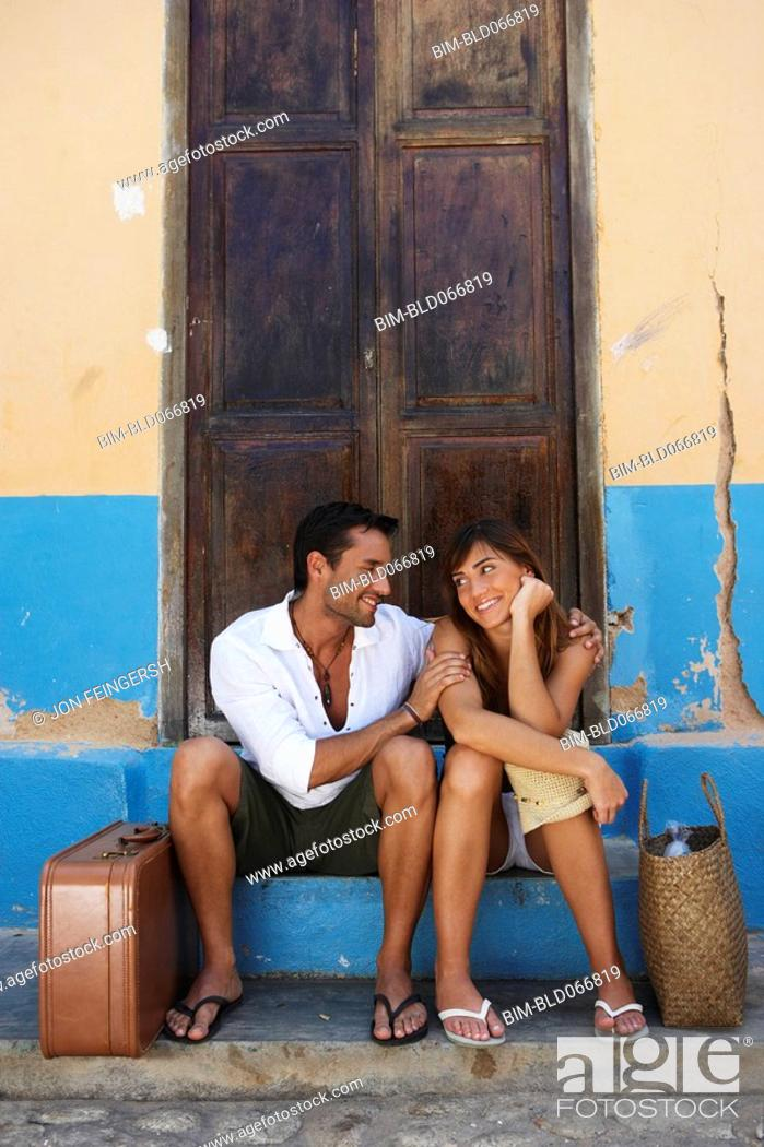 Stock Photo: Couple sitting with suitcases.