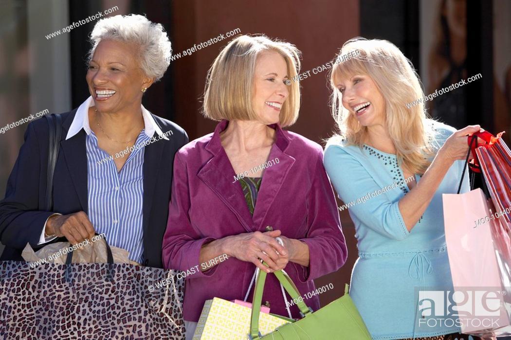 Stock Photo: Smiling Women walking outside carrying bags on Shopping Trip.
