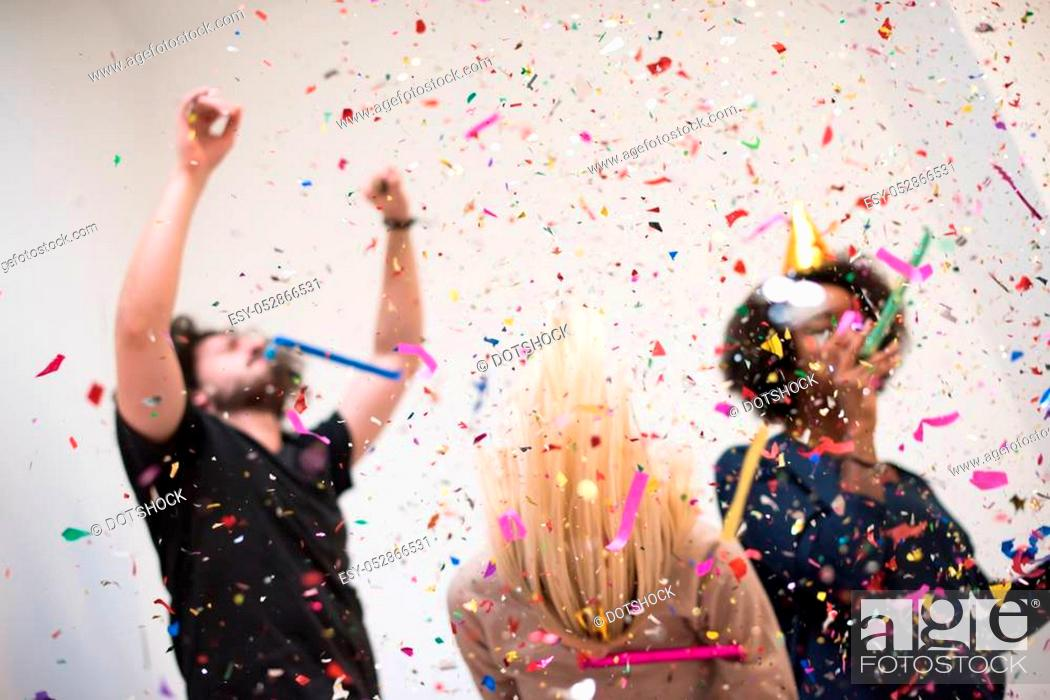 Stock Photo: confetti party happy young people group celebrating new year eve while dancing and have fun at home.