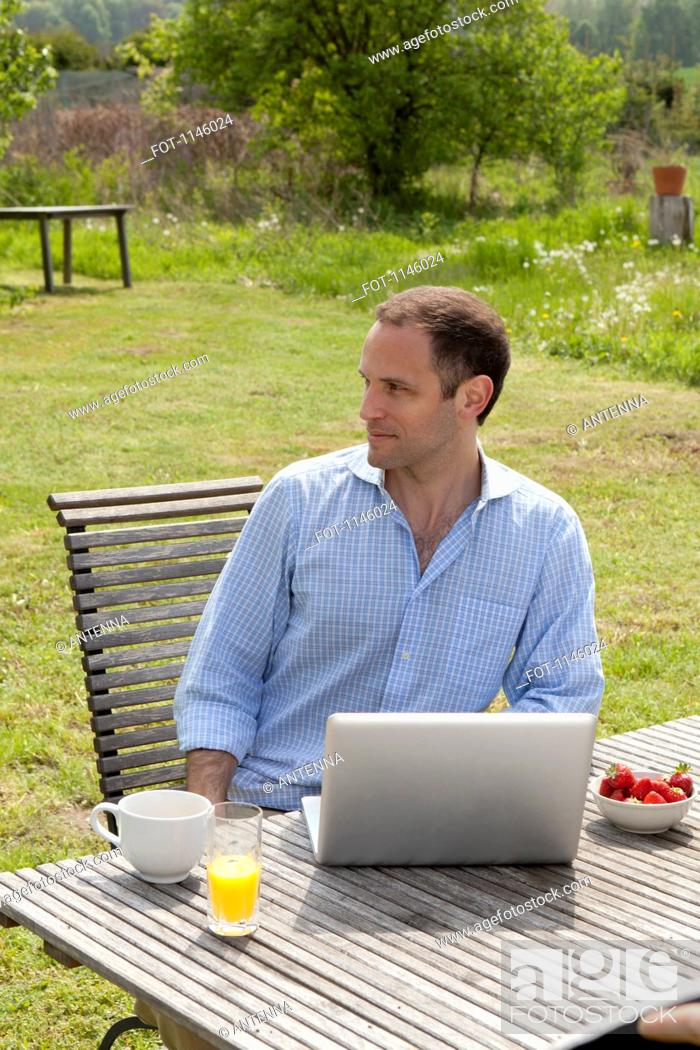 Stock Photo: A man sitting at a table in his backyard having breakfast and using a laptop.