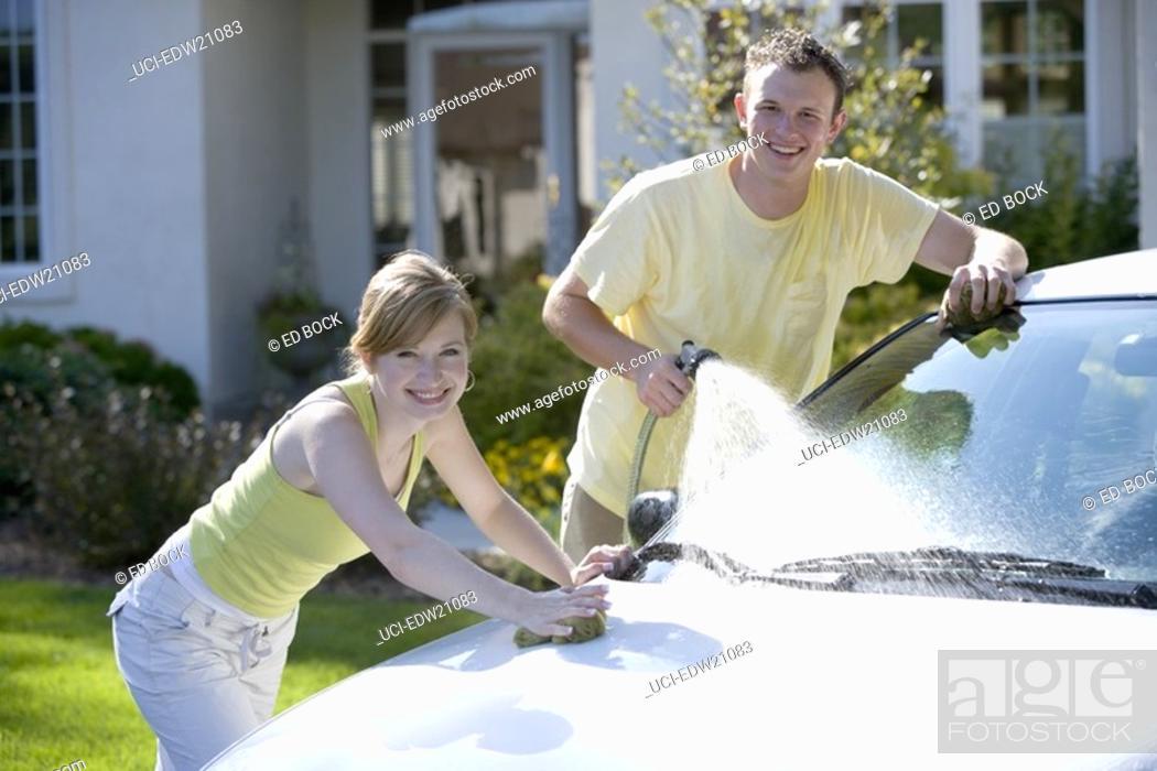 Imagen: Young couple washing car.