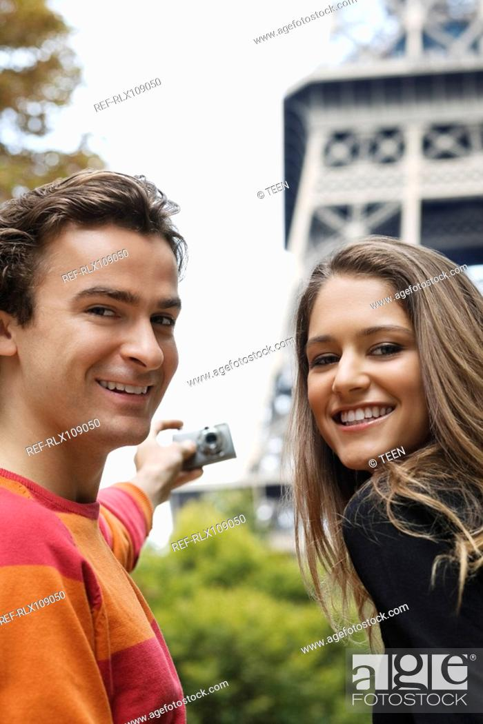 Stock Photo: Young couple taking self portrait with Eiffel tower in background, Paris, France.