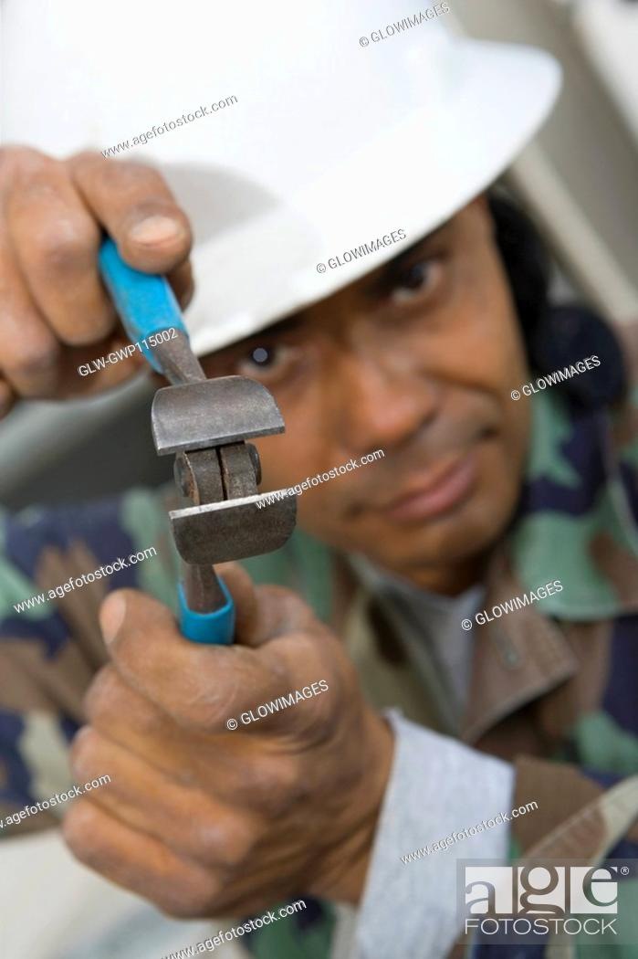 Stock Photo: Portrait of a mature man holding a wire cutter.