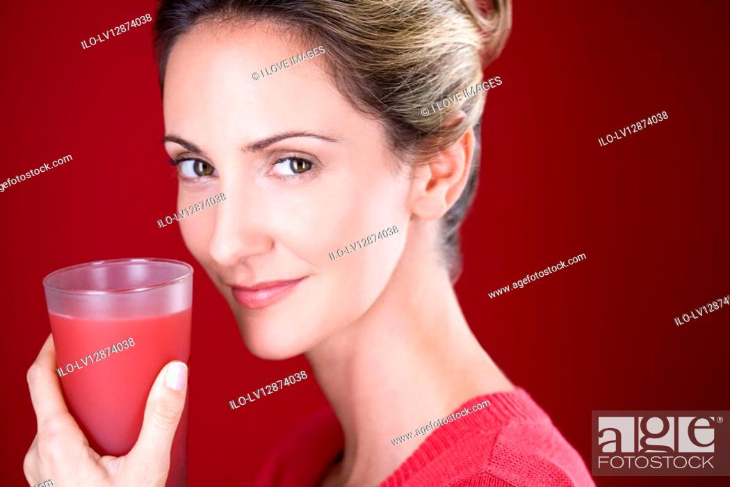 Stock Photo: A mid adult woman holding a glass of fruit juice.