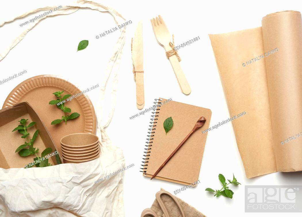 Stock Photo: textile bag and disposable tableware from brown craft paper, green mint leaves on a whitebackground. View from above, plastic rejection concept, zero waste.