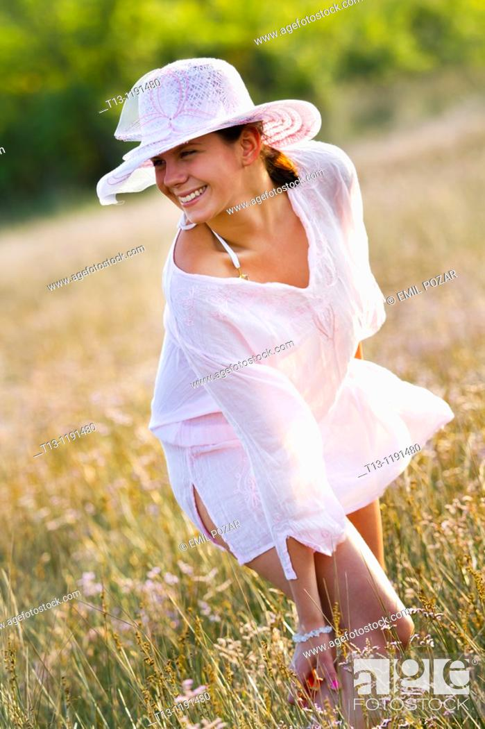 Stock Photo: Pretty in a white robe in the field young woman.