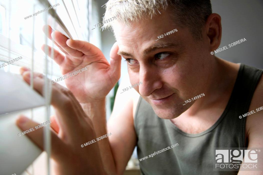 Stock Photo: Man looking through blinds.