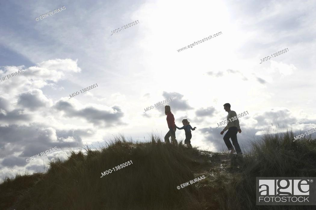 Stock Photo: Silhouette of parents and daughter 5-6 walking on sand dunes.