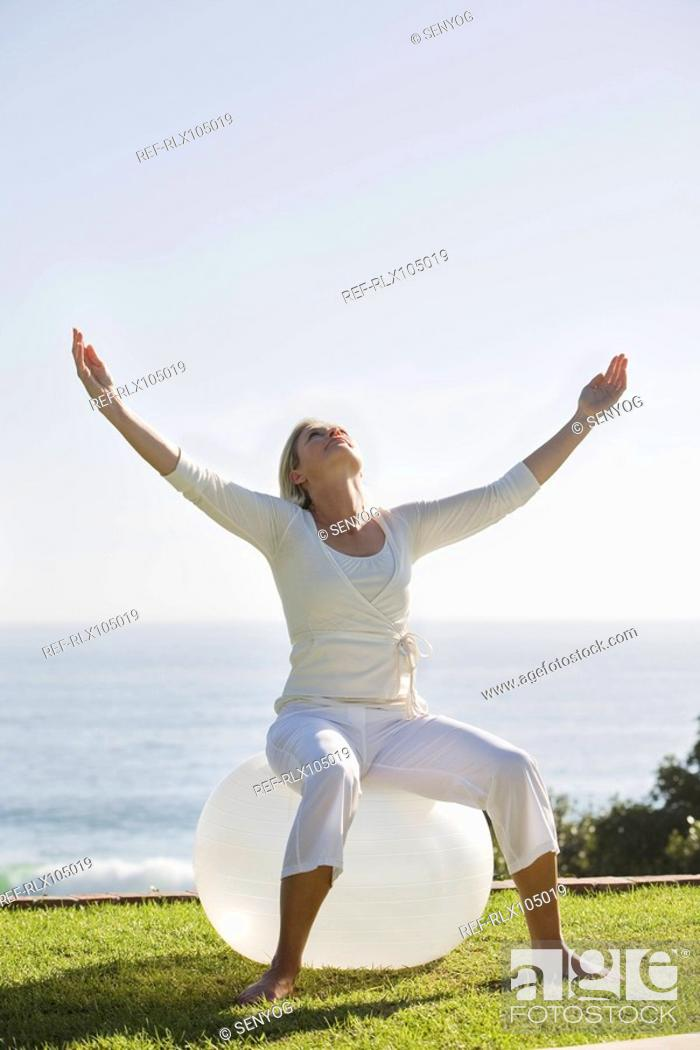 Stock Photo: Mature woman with arms outstretched sitting on exercise ball in garden.