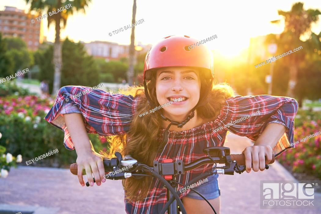 Stock Photo: Girl portrait on bicycle with helmet smiling happy at the flowers park outdoor.