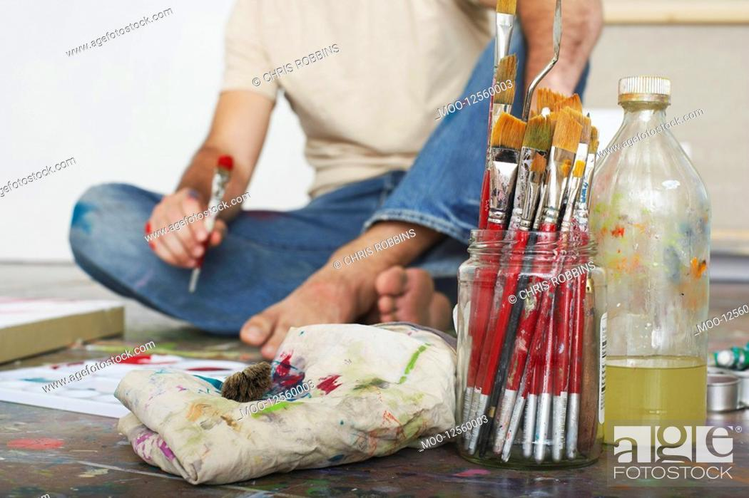 Stock Photo: Artist sitting on floor focus on paint brushes and materials.
