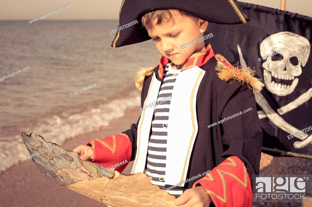 Stock Photo: One happy little boy playing on the beach at the day time. He are dressed in pirate costume. Kid having fun outdoors. Concept of sailor on vacation.