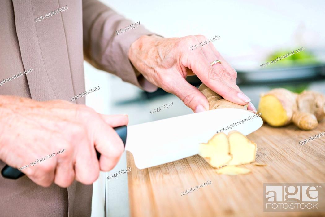 Stock Photo: Close up of senior female hands chopping ginger.