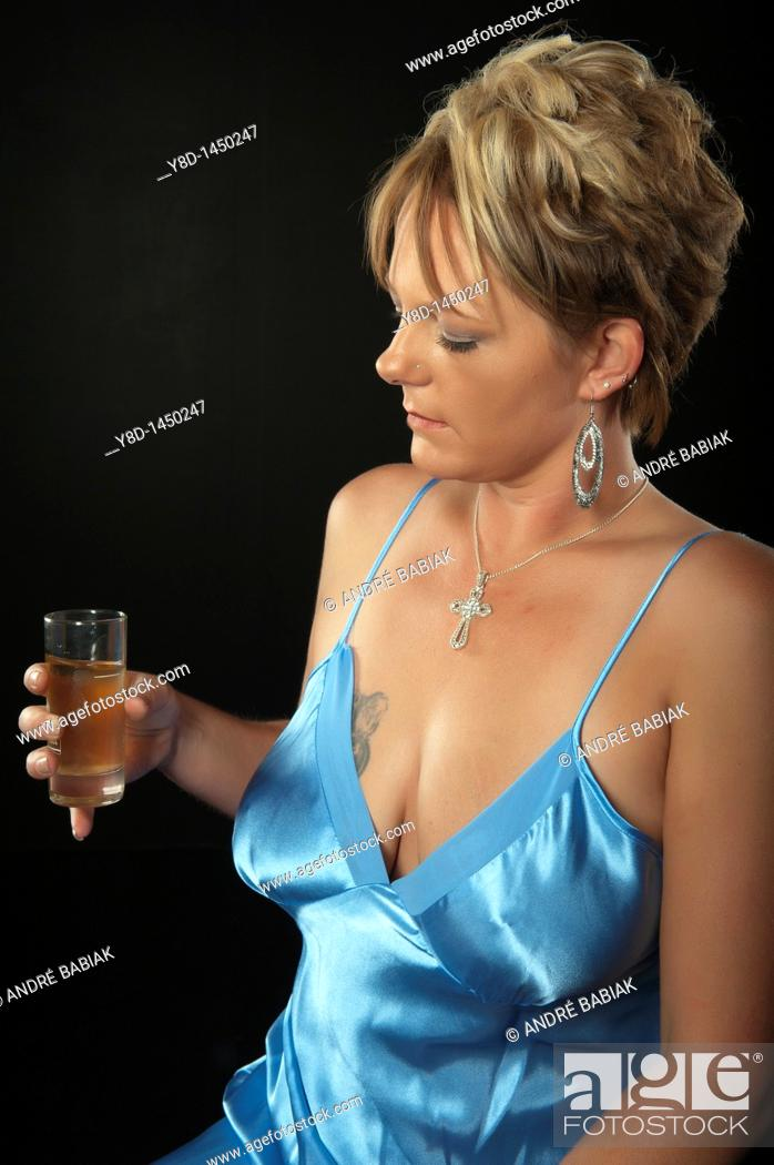 Stock Photo: Woman in night gown having drink.