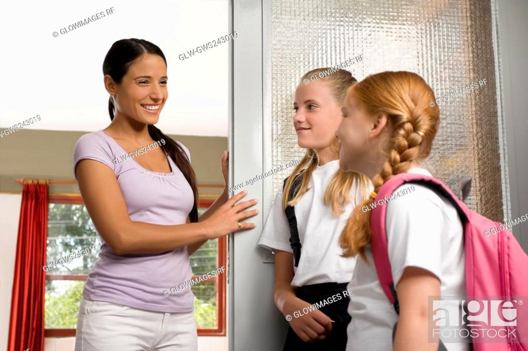 Stock Photo: Two schoolgirls with a female teacher looking at each other and smiling.