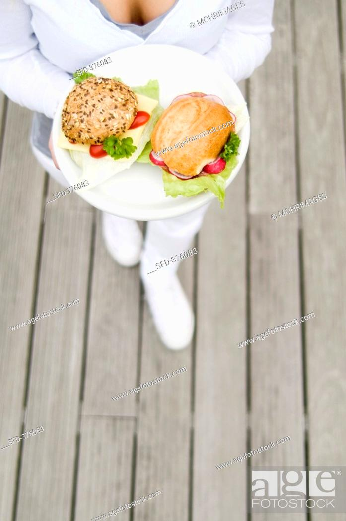 Stock Photo: Young woman holding two filled rolls on a plate.