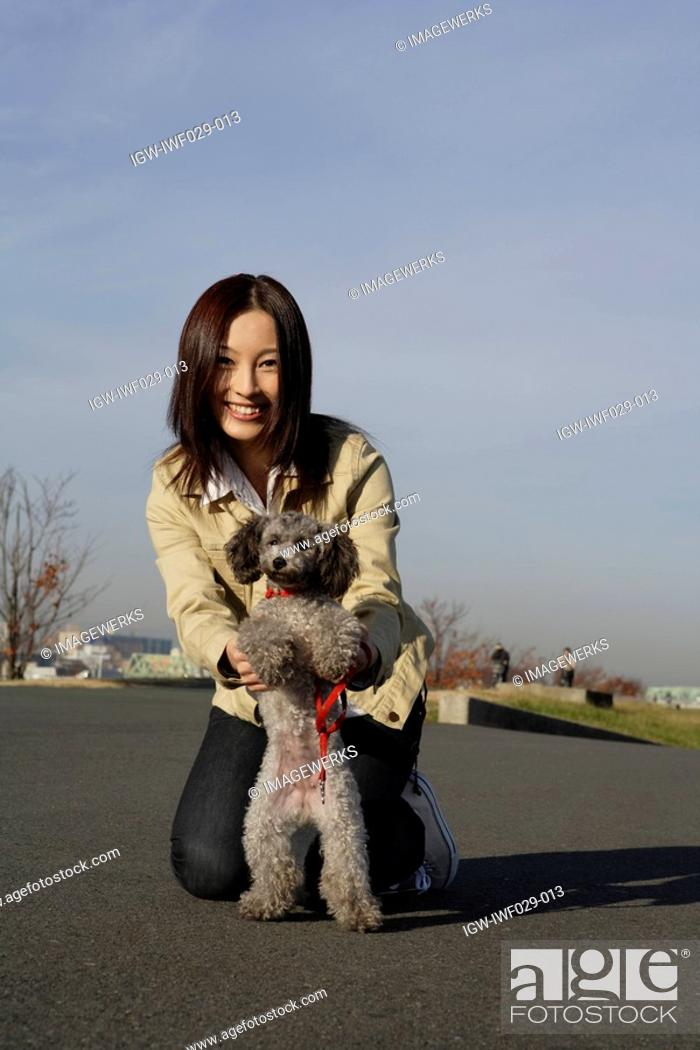 Stock Photo: Portrait of a young woman with her pet dog.