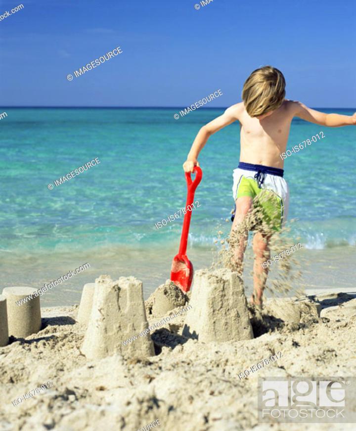 Stock Photo: Boy smashing sandcastles.