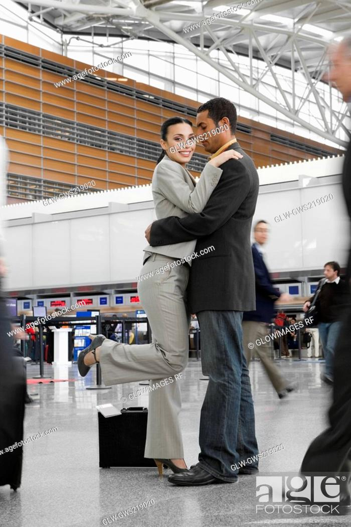 Stock Photo: Side profile of a businessman and a businesswoman hugging each other at an airport.