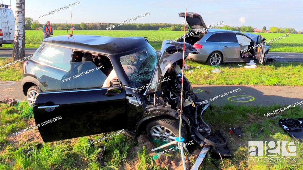 Stock Photo: 28 April 2019, Lower Saxony, Wildeshausen: Two destroyed cars are standing on a country road after a frontal collision. Two people were killed in the accident.