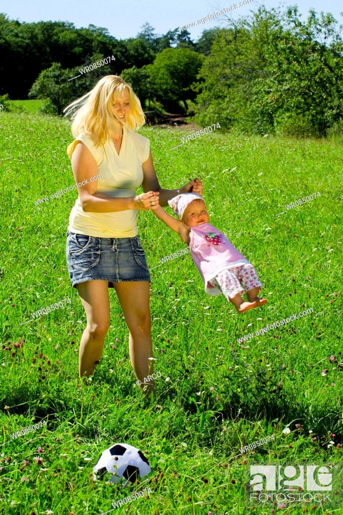 Stock Photo: Young mother playing with daughter, flying in circles.