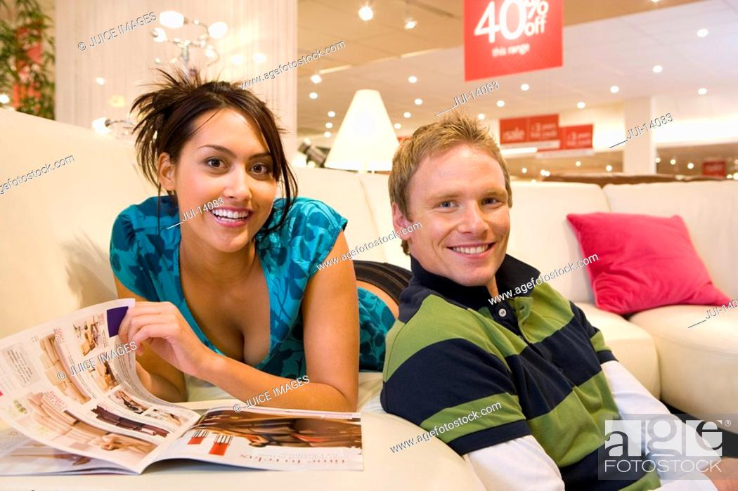 Stock Photo: Young woman with brochure on sofa in shop by man, smiling, portrait.
