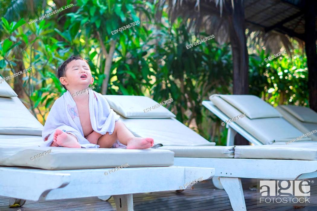 Stock Photo: Asian boy with white towel resting on a lounge deck chair or sun lounger near swimming pool with big tree and sun light. on summer holidays.