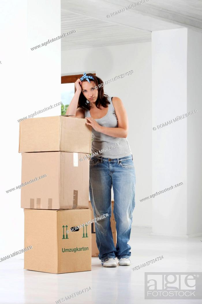 Stock Photo: Young woman leaning on cardboard boxes, portrait.