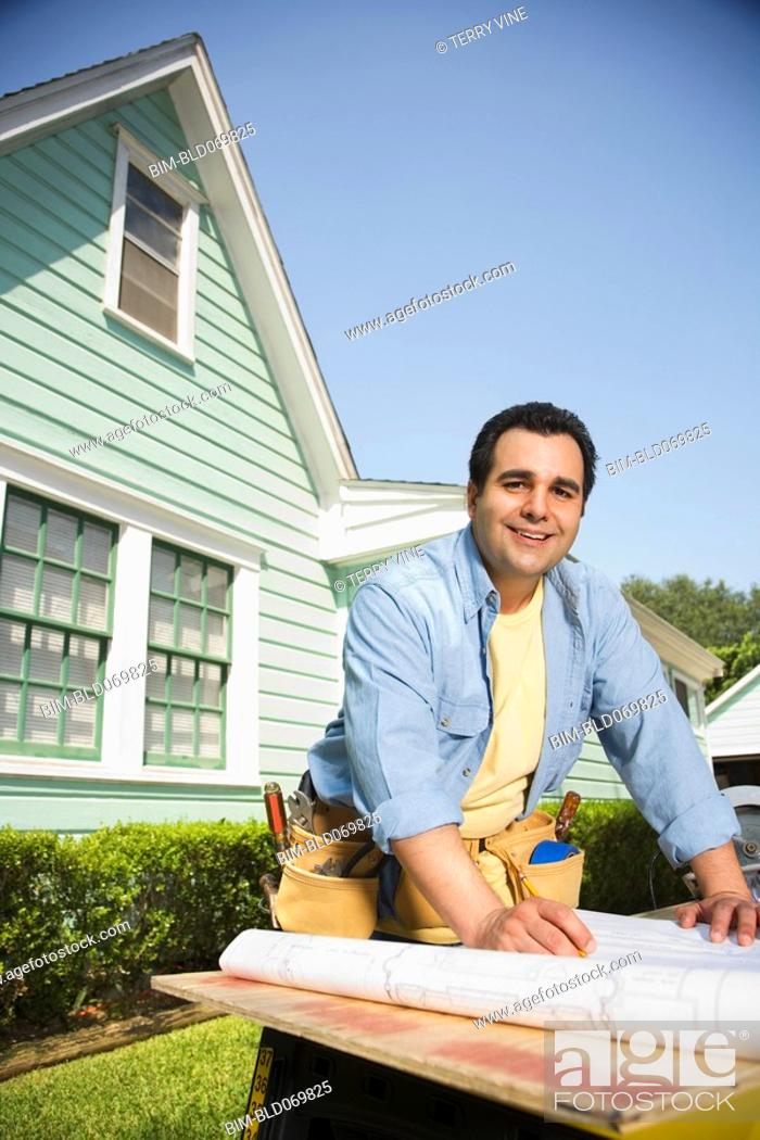 Stock Photo: Hispanic man with blueprints and tools outdoors.