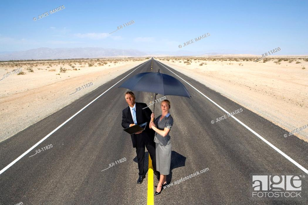 Stock Photo: Businessman and woman on open road in desert, man with laptop computer, woman with umbrella, elevated view.
