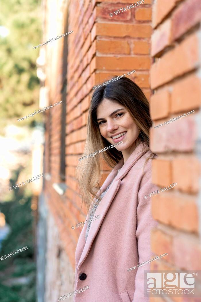 Imagen: Portrait of a happy young woman at a brick building.
