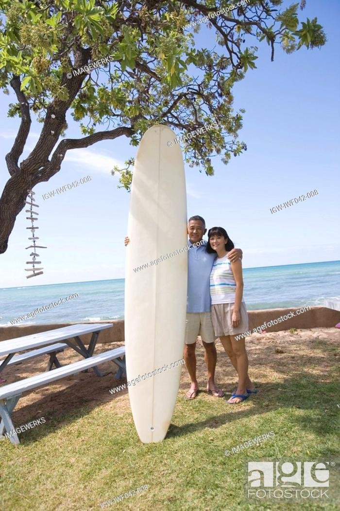 Stock Photo: A couple with surfboard smiling.